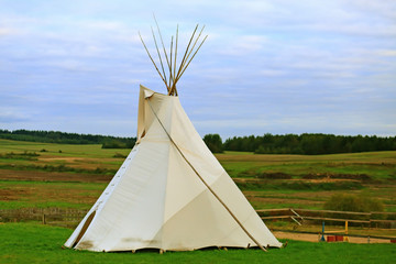 White wigwam on green field