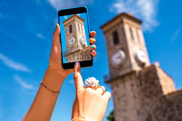 Holding smart phone with Notre-Dame church tower on the photo in Cannes in France. This church is a popular tourist attraction in Cannes