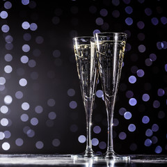 Fototapete - Two glasses of champagne on dark bokeh background
