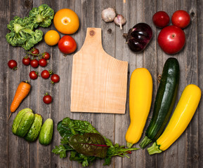 Fresh vegetables and ingredients for cooking around cutting board