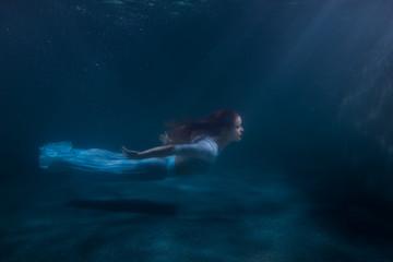 Woman as the mermaid under water.