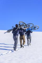 eine Gruppe Radfahrer trägt das Rad im Schnee bergauf