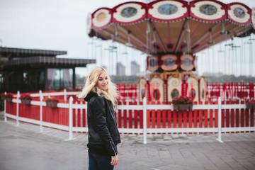 beautiful girl near the Red carousel on the street