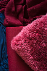 Cosy and warm textiles for fall decor:  sheepskin cushion and knitted blankets. Selective focus.