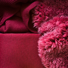 Cosy and warm textiles for fall decor: sheepskin and knitted blankets. Selective focus.