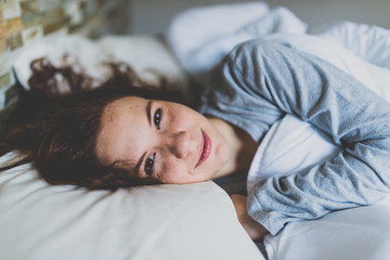 Ginger woman smiling at camera while lying under duvet in bed