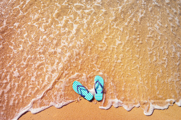 Vacation concept. Top view of blue flip-flops on the beach in sea wave.