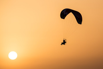 Silhouette of a Propelled Paraglider on a clear sunset sky