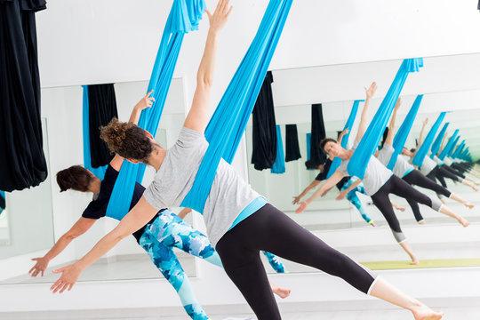 Women doing aerial yoga.