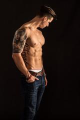 Tätowierter muskulöser Mann mit freiem Oberkörper schaut sinnlich - Junger Mann mit Sixpack auf schwarzem Hintergrund