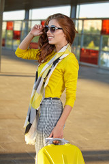 Happy travel by train. Stylish young women in yellow.