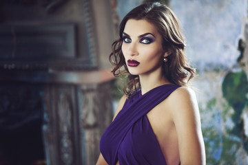 Beauty Brunette model woman in evening purple dress. Beautiful fashion luxury makeup and hairstyle.
