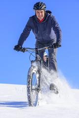 Mountainbiker hat Spass im Schnee