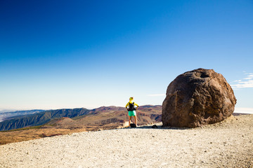 Woman hiking climbing in mountains in Spain. Looking at inspirational volcanic landscape.