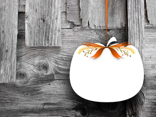 Close-up of one blank pumpkin shaped frame hanged by brown ribbon on gray wooden boards background