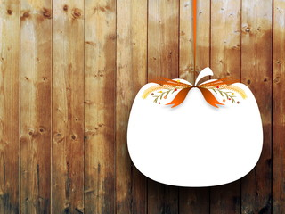 Close-up of one blank pumpkin shaped frame hanged by brown ribbon on vertical wooden boards background