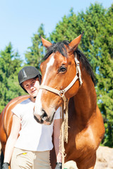 Young teenage girl equestrian standing with her brown horse