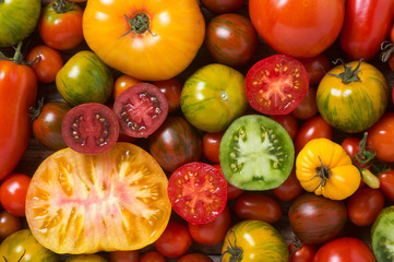 Close up of colorful tomatoes, some sliced, shot from above