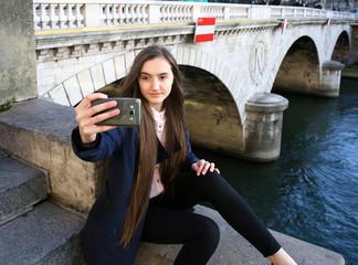 Beautiful young tourist girl making selfie near the bridge in Paris