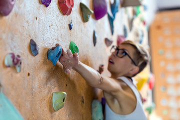 Young Female Climber on wall of indoor climbing gym
