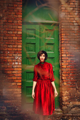 Girl in red retro dress on a background of vintage wooden door.