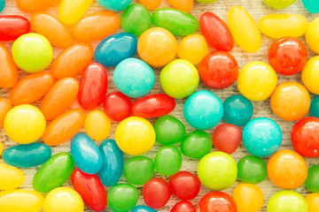 Colorful jelly beans close to wallpaper