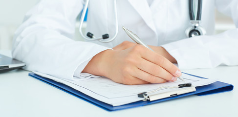 Female doctor is sitting at the table and filling up medical application form. Health care, insurance and help concept.