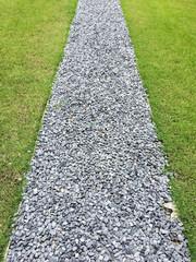 Gray gravel walking path in a grass field/lawn of a garden
