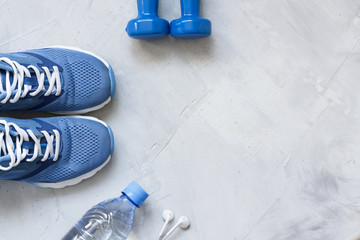 Flat lay sport shoes, bottle of water, dumbbells and earphones o