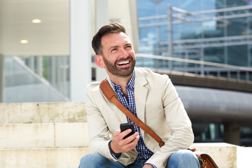 Laughing mature man sitting outdoors with cellphone