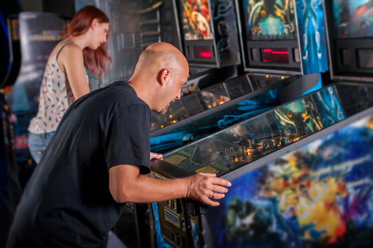 Young man playing pinball