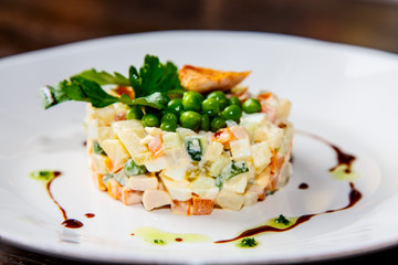 "Traditional Russian salad ""Olivier"" is on the plate"