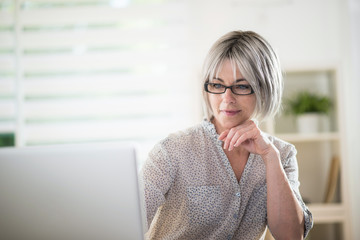 a  senior woman with glasses, who is studying  english lessons