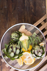 Ripe organic artichokes with lemon and ginger in metallic sieve on the rustic wooden lattice