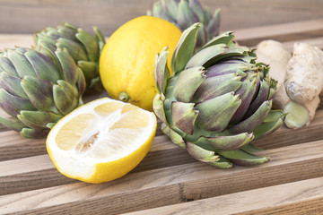 Ripe organic artichokes with lemon and ginger on the rustic wooden lattice