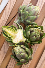 Ripe organic artichokes on the rustic wooden lattice