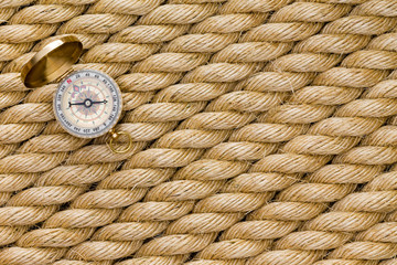 Small magnetic compass on diagonal strands of rope