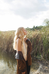 Beautiful blonde woman wearing flared jeans, a white lace top and a brown jacket, posing on the lake. Hippie, Boho Style. Baby's face model