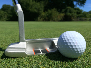 Generic white golf ball and iron putter line up on the green grass of a golf course. Aim and put into the hole.