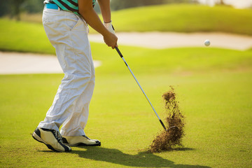 Golfer hitting ball with force. The grass distribution The blur