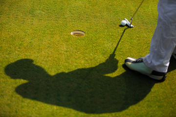 Shadow of golfer That is going to putt a golf ball