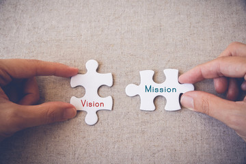 "Hands with puzzle pieces and ""Vision and Mission"" words"