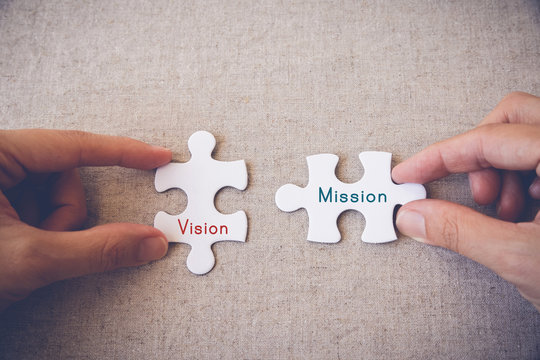 """Hands with puzzle pieces and """"Vision and Mission"""" words"""