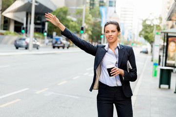 Portrait of business woman catching taxi