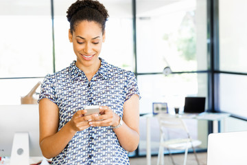 Portrait of smiling afro-american office worker in offfice with mobile