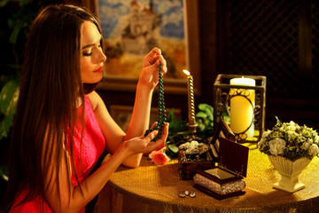Woman in her home puts necklace on her neck . Romantic evening on luxary interior background.