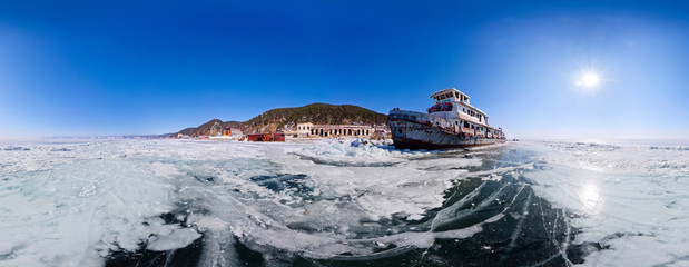 Old rusty ship on the coast of Lake Baikal among ice. Panorama 3