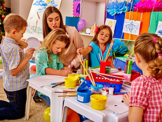 Children with teacher woman painting school on paper at table in kindergarten . Interior of kindergarten or primary school.