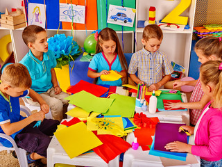 Group of school children are making something out of colored paper on table in primary school. Children craft lesson in primary school. Development children craft at class in school.