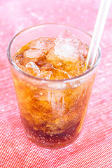 Coke or Pepsi and ice in glass.